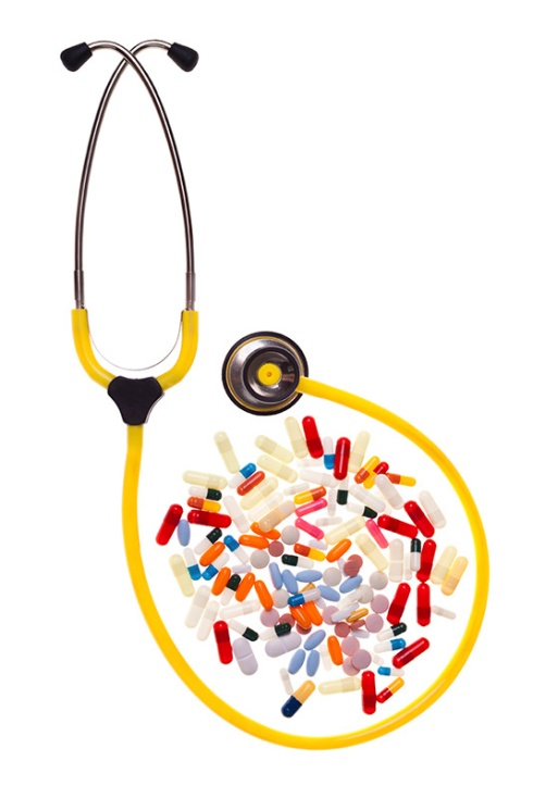 many pills and capsules over white surrounded by a yellow stethoscope